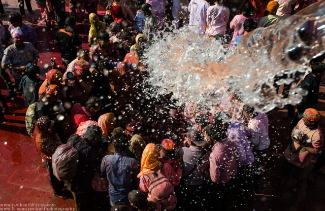 Water being splashed on a group of photographers and the locals playing Holi.