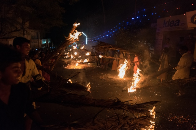 Villagers burning dry coconut leaves while welcoming the kolam procession.